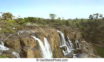 girl holds yoga pose on rocks against waterfall