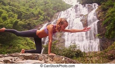 Girl Holds Yoga Position by Foamy Waterfall in Jungle