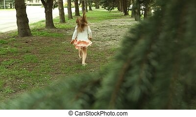 Girl hopping and runs away from camera among straight lines of pine trees in park
