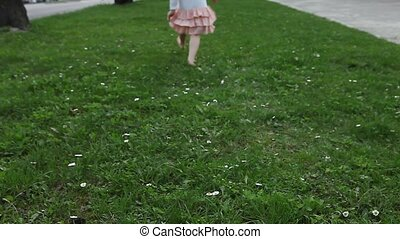 Girl hopping and runs away from camera on greem lawn outdoor