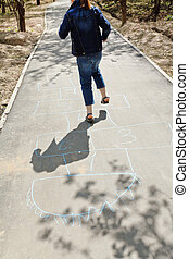 girl hopping in hopscotch on urban alley