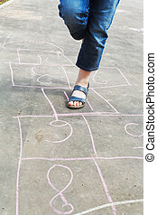 girl hops in hopscotch outdoors