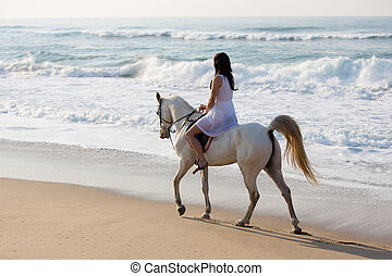 girl horse ride on the beach - girl in white dress enjoying...