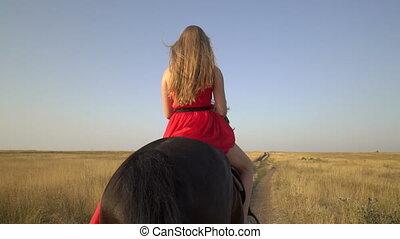 Girl horseback rider wearing long red dress riding horse on...