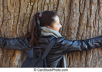 Girl hugging a big tree. Force of nature, ecology. Back view.