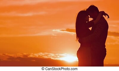 girl hugging a man at sunset slow motion video