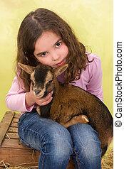 Girl hugging baby goat