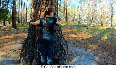 Girl hugging big tree. Slow motion, 4K