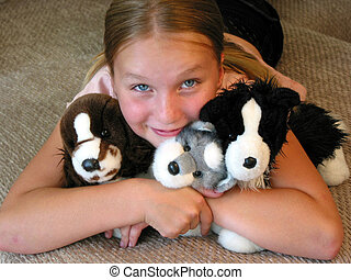 Happy young girl with her favourite plush toys.