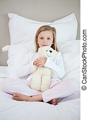 Girl hugging her teddy on the bed
