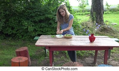 girl hulled green organic peas sitting at wooden table yard. 4K