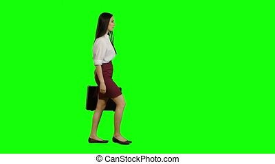Girl hurries to important negotiations, in her hand a diplomat with documents. Green screen