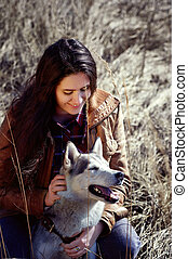 Girl husky is scratching behind the ear and smiles .