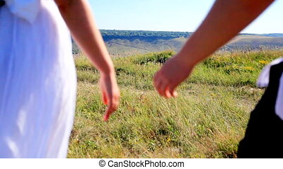 girl i and guy walking on the bank of wide river on summer day.
