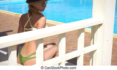 girl in a bathing suit with beautiful body adjusts his shorts by the pool