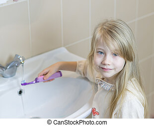 Girl in a bathroom washes electric toothbrush.