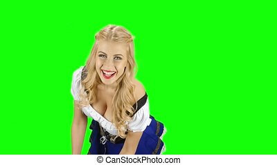 Girl in a bavarian costume and offers someone for the glasses with beer. Green screen