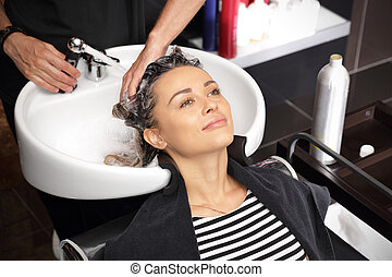 Girl in a beauty salon relaxes - a hairdresser's hands wash ...