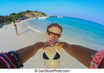 Girl in a bikini on the beach makes selfie.