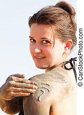 girl in a bikini rubs mud