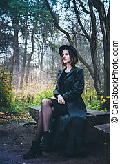 girl in a black coat sitting on a bench
