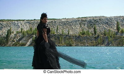 A fat girl in a black dress and a cylinder is standing on the shore of the sea. She removes the black celinders with a black veil developing on it. Slow motion.