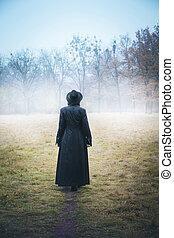 Girl in a black long coat in the fog