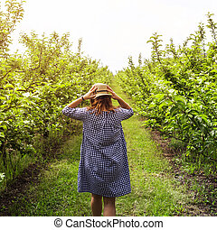 Girl in a blue dress in a green apple orchard