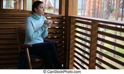 girl in a blue sweater sitting on a wooden chair and drinking tea