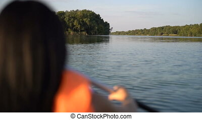 Girl in a boat rowing an oar. Slow motion - A girl floats in...