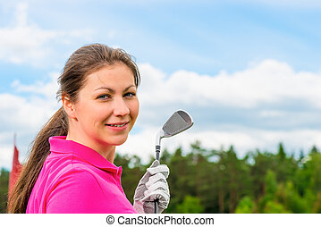 girl in a bright pink T-shirt with a golf club