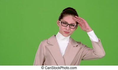 Girl in a business suit is standing in the studio, she has terrible headache. Green screen