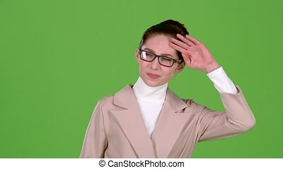 Girl in a business suit is standing in the studio, she has terrible headaches. Green screen. Slow motion