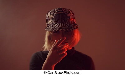 Girl in a cap moving in the studio in the smoke