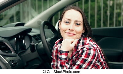 Girl in a car smiling and looking at camera
