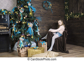 Girl in a chair on the background of the Christmas tree