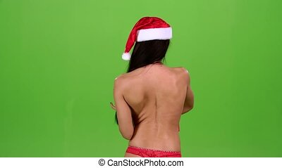 Girl in a Christmas hat turns with a gift in her hands. Green screen. Slow motion