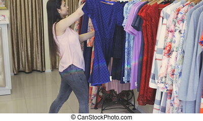 Girl in a clothing store chooses a dress