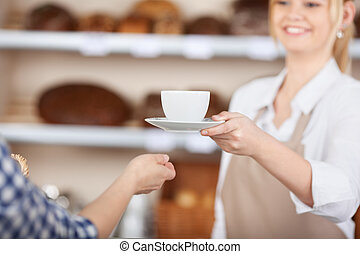 girl in a coffeehouse serving a cup of coffee