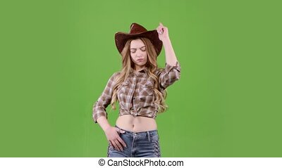 Girl in a cowboy hat is dancing. Green screen