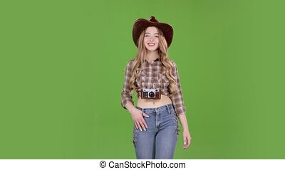 Girl in a cowboy hat walks and photographs beautiful...