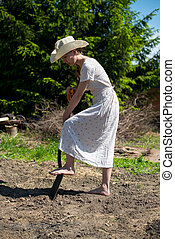 girl in a cowboy hat with shovel digging hole