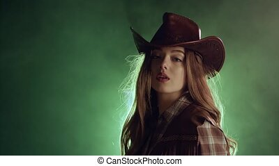 Girl in a cowboy's clothes is dressing a hat. Black smoke background. Slow motion