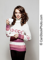 Girl in a crocheted clothes with cup of coffee