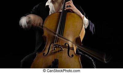 Girl in a dark room plays a cello rehearsing a composition....