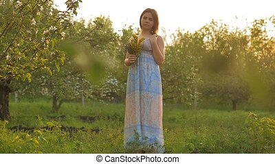 girl in a dress in the garden with a bunch of slow-motion video