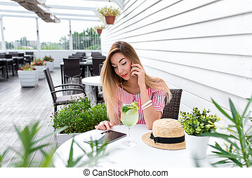 Girl in a dress sitting in a city cafe in summer. Calls on phone and looks at the tablet. Against the background of a white wall and green plants. On the table is a glass with green lime and lemon.