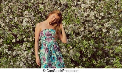 girl in a dress smiling near blossoming tree
