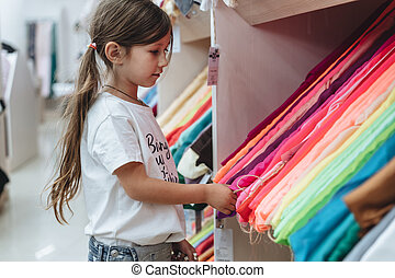 Girl in a fabric store chooses a multi-colored fabric - A...