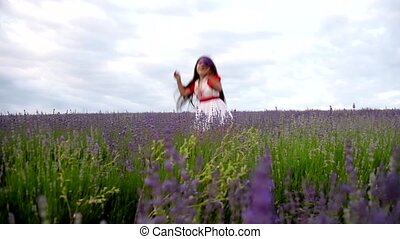 Girl in a field of lavender fun screams and slaps hands.